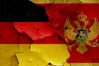 flags of Germany and Montenegro painted on cracked wall