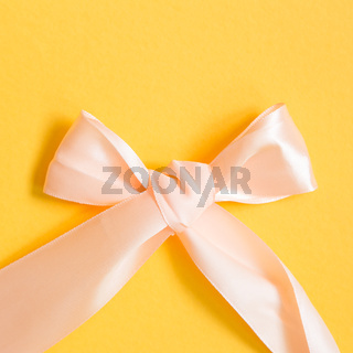 Peach color ribbon on yellow background