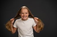 Happy smiling and holding two pony tails 8,10 years old girl holding her hair wearing white t shirt smiling a little grinning at the camera isolated on dark grey or black background