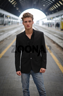 Attractive blue eyed, blond young man standing inside train station