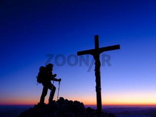 Silhouette eines Bergsteigers mit Siegerpose am Gipfelkreuz bei Morgendämmerung