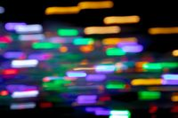 Multicolored spots of light in motion blur against black background