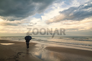 A woman with umbrella in the rain by the sea