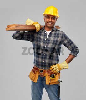 happy indian worker or builder with wooden boards