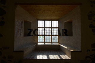 Portrait of closed wooden window and ceiling with sunlight streaming in