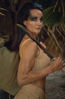 Female holding machete posing on wild nature of palm trees forest. Spirit of adventure. Survivor woman concept