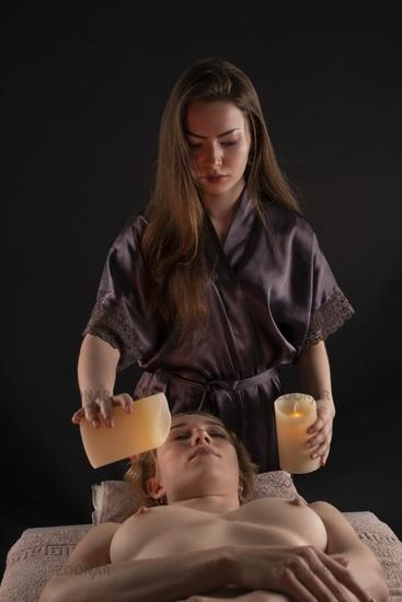 woman enjoying candle massage in spa salon