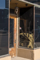 Cracked and damaged window pane by door to retail shop in downtown area