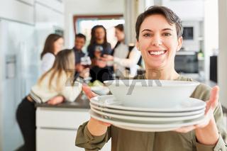 Frau mit Geschirr beim Tisch decken vor Freunden in Küche