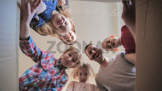 A large family opens the box in their home.