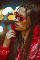 Young girl with glasses outdoor fashion portrait with braided hair wears red down jacket and fashion on neon street lights. Night club fashion. Girl and neon lights