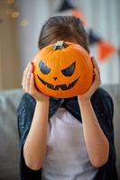 girl in halloween costume with pumpkin at home