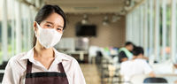 Panorama Portrait of waitress with facemask in New normal restaurant background