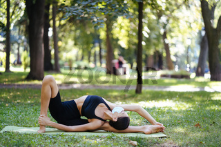 Athletic young woman in a medical protective mask, doing yoga in the Park