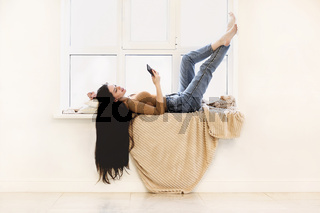Young woman with smartphone lying on windowsill