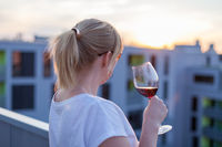 Blonde woman standing on a terrace and drinking some red wine at sunset