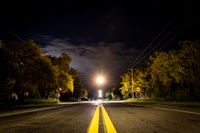 Perspective view of yellow lane lines of an old asphalt road in a lonely quiet night, with storm coming from the clouds