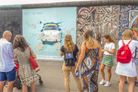 visitors at east side gallery, trabi car breaking through wall