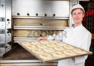 Baker with baking plate full of pretzels