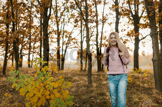 Traveling girl with a backpack smiles standing on beautiful autumn forest background. Caucasian blonde travels on nature on a sunny day. Hiking concept