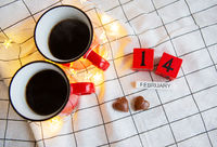 Two cups of coffee in red cups on a background of chocolate canfet in the form of a heart. Morning surprise for Valentine's Day. View from above.