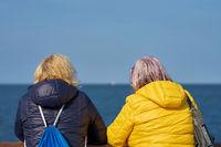two women during a conversation at a bridge railing