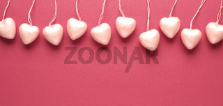 10 heart hanger in a row on red background.