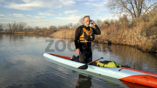 Stand up paddler making a phone call after paddling workout.