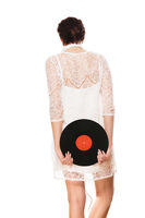 woman holding vinyl record behind her back