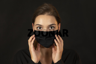 Attractive young woman in a black protective mask on dark background.
