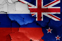 flags of Russia and New Zealand painted on cracked wall