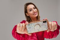 Happy young woman showing shiny mobile phone