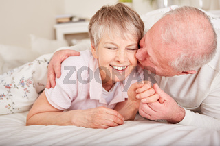 Paar Senioren küssen sich im Bett
