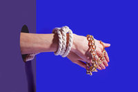 Pair of hands tied by rope and golden chain