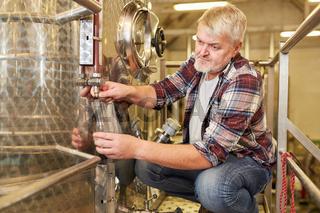 Winzer kontrolliert Wein am Gärtank in Weinkellerei