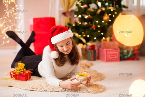 Beautiful teenage girl opening her christmas present