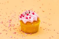 Decorating a Cupcake with Sprinkles on orange pastel background.