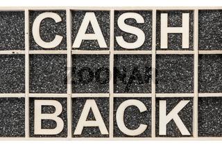 Wooden word CASH BACK on black sand