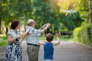 Happy elderly couple with a grandson on a walk. An elderly husband and wife and child launch a drone.
