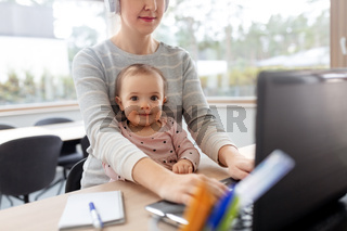 mother with baby working on laptop at home office