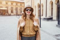 Charming girl in an autumn beige coat and sunglasses walking on the street with coat on her shoulders. Toned photo