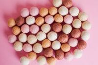 Multicolor felt balls spilled on pink cover