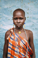 TOPOSA TRIBE, SOUTH SUDAN - MARCH 12, 2020: Girl in checkered colorful garment and with traditional accessories looking at camera against blue wall in Toposa Tribe village in in South Sudan, Africa
