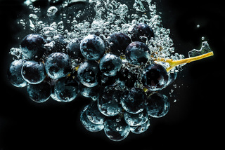 Bunch of red grapes splashing into clear water isolated against black background. Food splash photography