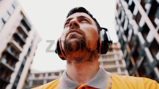Builder covers his ears, ear muff to protect workers ears. Construction worker wearing protective ear defenders. Concept of construction, taking care of safety during work. Protection against injury