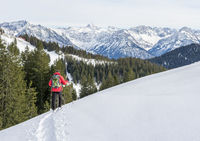 Senior man is snowshoe hiking in alpine snow winter mountains. Allgau, Bavaria, Germany.