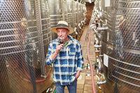 Winzermeister mit Glas Rotwein vor einem Gärtank