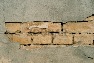 Texture of outer wall with fallen plaster. Old building with falling off plaster. Background of brick wall pattern