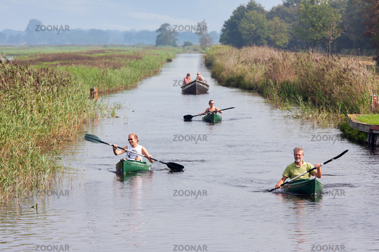 People pedaling in canoes through wetlands Dutch National Park Weerribben