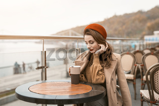 Thoughtful young woman looking at cup of coffee wearing red beret sitting on the terrace of a restaurant or cafe on background of an autumn urban city